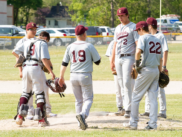 Record-Eagle/Brett A. Sommers<br /> <br /> Traverse City Christian coach Hank Burch and the rest of the infiield visit the mound to speak with pitcher Grant Maurer during the opening baseball game of Monday's  doubleheader against Buckley.