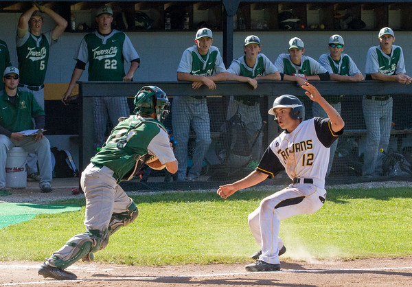 Record-Eagle/Brett A. SommersTraverse City Central's Logan Briggs runs into Traverse City West catcher Alex Strickland for an out during Friday's district championship game at Central High School.