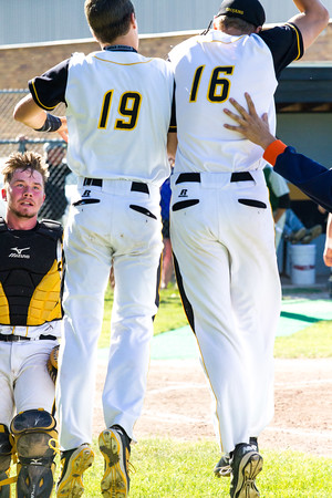 Record-Eagle/Brett A. SommersKlug brothers, Luke (19) and David (16), celebrate David's inning-ending strike out during Friday's district championship game against Traverse City West at Central High School.