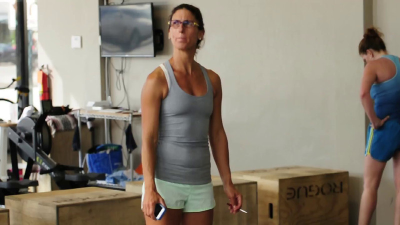 Coach Jen Rulon, Triathlete Coach and Ironman, spotting one of her athletes during a 'Strongest Mile' strength training session at King William District CrossFit in San Antonio, Texas on 29 May 2014. The Strongest Mile is a strength and conditioning program designed for endurance athletes by an endurance athlete, Coach Rulon herself. More info at jenrulon.com.