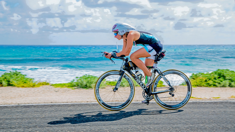 """Racing during the cycling stage of the 2013 Ironman Cozumel along the Playa Oriente. This image has been cropped to a 16 w x 9 h format, which will yield a bit of a panoramic print on canvas or metal. A bit more could be cropped from the top and bottom to create an image that is even more rectangular (i. e., 16"""" w x 32"""" h). This image has a """"painterly"""" quality added in post-production processing to enhance detail."""