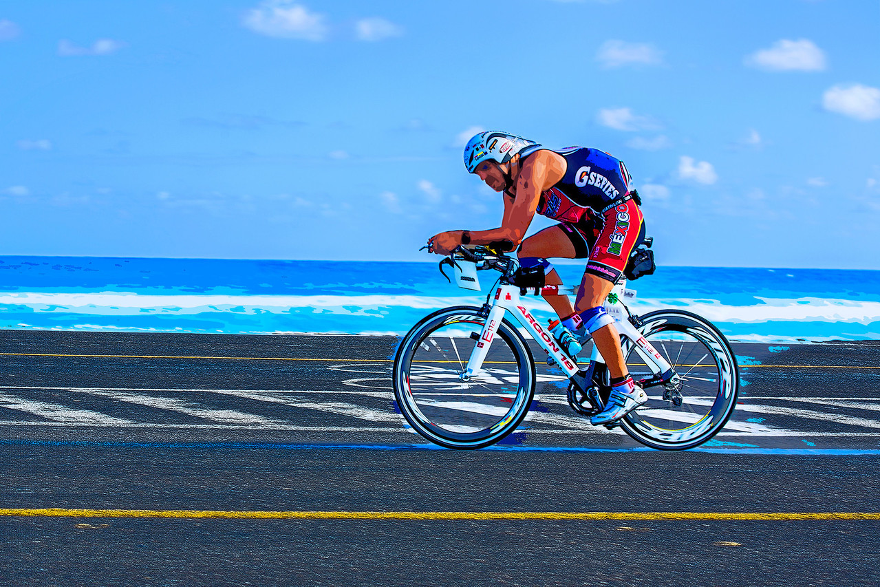 Against the Wind… A lone cyclist sports the colors of Mexico and rides into the wind during the 112-mile cycling stage of Ironman Cozumel 2013 along Playa Oriente near Mezcalitos on the east side of the island.