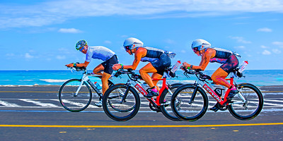 "The Overtake… Racing during the 112-mile cycling stage of Ironman Cozumel 2013 along the Playa Oriente area of Punta Morena near Mezcalitos on the east side of the island. This image is composed to ideally yield a 16"" x 32"" print or canvas or any other 1:2 ratio size such as 12"" x 24""."