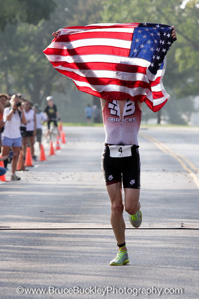 First finisher, Dan Feeney, runs through the finishing straight, holding up the U.S. flag.