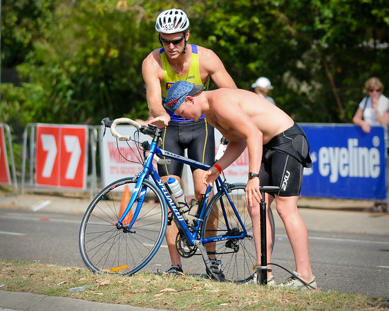 """The guy helping had actually been in the race and joined his mates beside me just after finishing the cycle leg. The cyclist appreciated his help and shook his hand. - 2008 Noosa Triathlon, Noosa Heads, Sunshine Coast, Queensland, Australia. Photos by Des Thureson - <a href=""""http://disci.smugmug.com"""">http://disci.smugmug.com</a>"""