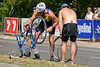 "The guy helping had actually been in the race and joined his mates beside me just after finishing the cycle leg. The cyclist appreciated his help and shook his hand. - 2008 Noosa Triathlon, Noosa Heads, Sunshine Coast, Queensland, Australia. Photos by Des Thureson - <a href=""http://disci.smugmug.com"">http://disci.smugmug.com</a>"