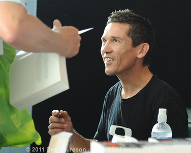 Aussie Cycling Champion Robbie McEwen autographs copies of his book at the Noosa Triathlon Multi Sport Festival, 29 October 2011; Noosa Heads, Sunshine Coast, Queensland, Australia.