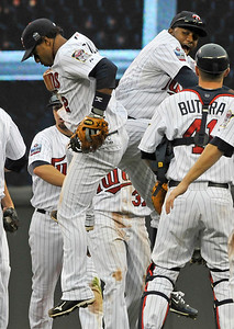 Minnesota Twins' Alexi Casilla, left, and Denard Span bump mid-air as they celebrate the Twins' 5-1 win over the Cleveland Indians in a baseball game Wednesday, Sept. 22, 2010 in Minneapolis. Casilla went 3-for-4. (AP Photo/Jim Mone)
