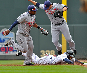 Cleveland Indians pitcher Carlos Carrasco, top right, jumps to avoid Minnesota Twins runner Ben Revere who was tagged out during a rundown between first and second by second baseman Louis Valbuena, left, in the second inning of a baseball game Wednesday, Sept. 22, 2010,  in Minneapolis. Carrasco was covering first during the rundown. (AP Photo/Jim Mone)