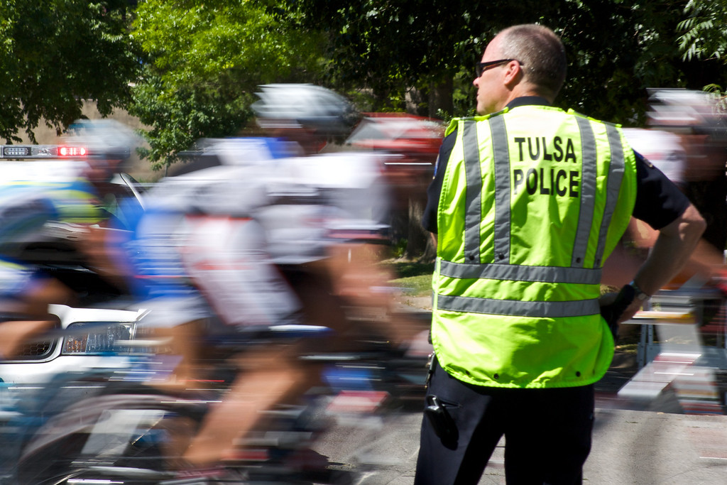 """A Tulsa Police officer watches the peloton cross a street during the 2009 Tulsa Tough race. Tulsa Police are responsible for keeping motorists off the street while cyclists are crossing, and assisting drivers with getting to their destinations quickly in-between laps while passing is safe. More details of the race can be viewed at <a href=""""http://blog.rjbphoto.com/2009/06/tulsa-tough.html"""">http://blog.rjbphoto.com/2009/06/tulsa-tough.html</a>"""