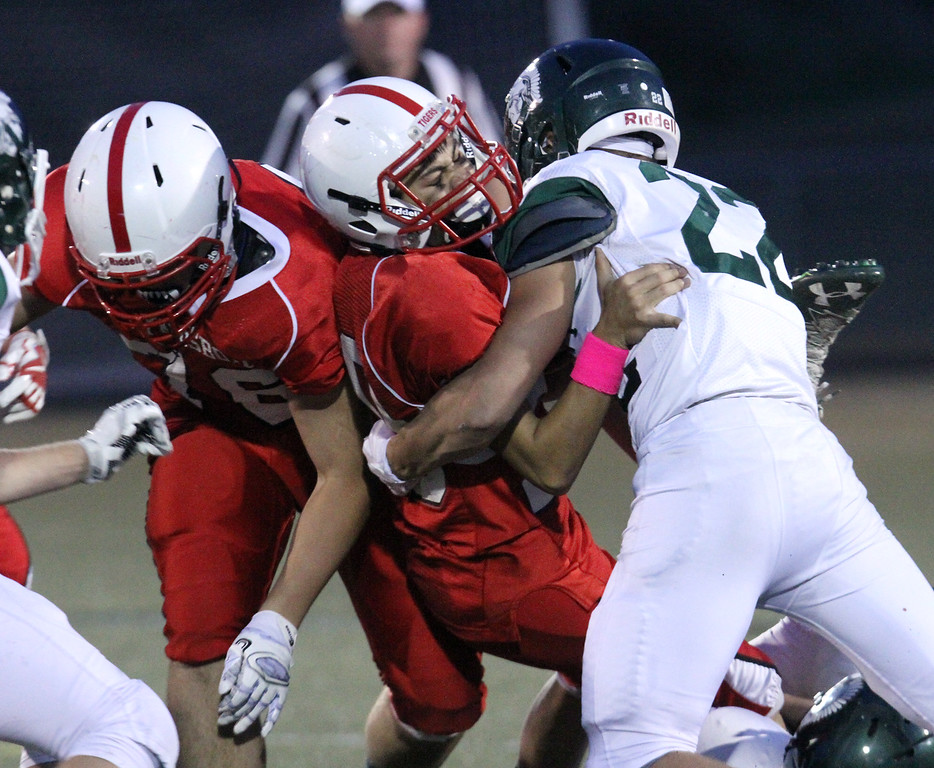 . Tyngsboro vs Oakmont Regional football. From left, Tyngsboro\'s Nicholas DeBruin (76) and Justin Huberty (20), carrying ball, tackled by Oakmont\'s Justin Jameson (22). (SUN/Julia Malakie)