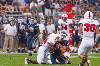 East Hartford CT Sept. 8 2012 Rentschler Field UCONN Huskies  Wide Receiver  31  Nick Williams catches a pass on his knees and is tackled by North Carolina State  defensive back  38  Hakim Jones and North Carolina State  safety  25  Dontae Johnson