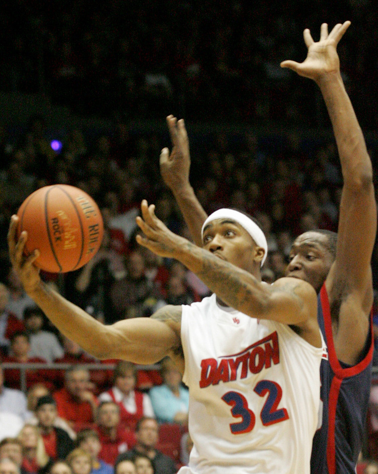 E.L. Hubbard for the DDN<br /> UD guard Marcus Johnson scores two despite the defense of Duquesne forward Damian Saunders in the first half at UD Arena Saturday, March 7, 2009.
