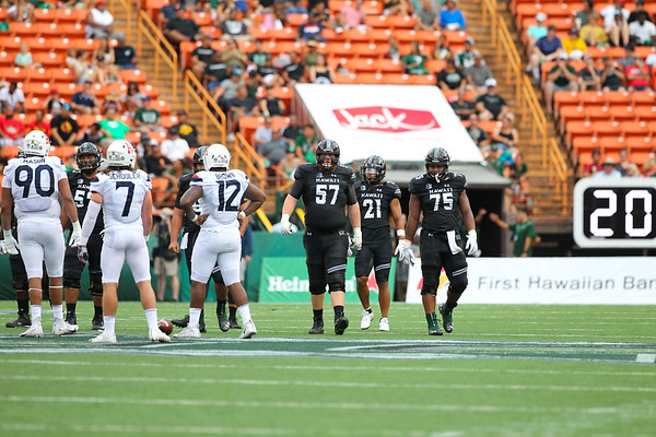 Hawaii offensive linemen J.R. Hensley (57) and Ilm Manning (75) approach the line of scrimmage while running back Fred Holly III waits in the backfield against Arizona at Aloha Stadium on August 24, 2019, in Honolulu, Hawaii.