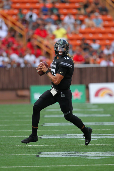 Hawaii quarterback Cole McDonald (13) looks to pass on the run against Arizona  at Aloha Stadium on August 24, 2019, in Honolulu, Hawaii.
