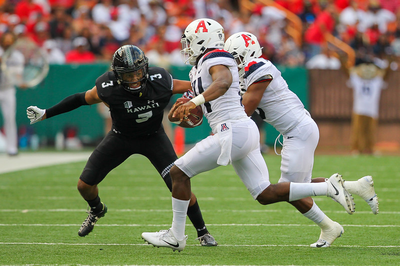 Hawaii's Kalen Hicks (3) looks to tackle Arizona quarterback Khalil Tate (14) after an 11 yard rush at Aloha Stadium on August 24, 2019, in Honolulu, Hawaii.