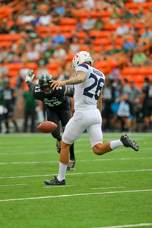 Arizona punter Matt Aragon punts as Hawaii's Ikem Okeke closes in at Aloha Stadium on August 24, 2019, in Honolulu, Hawaii.