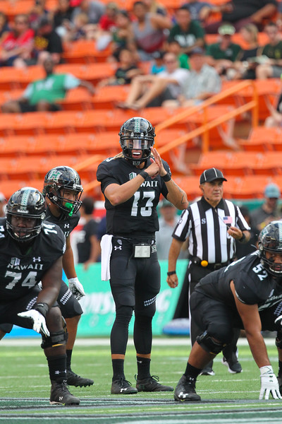 Hawaii quarterback Cole McDonald (13) surveys the defense before the snap against the Arizona Wildcats at Aloha Stadium on August 24, 2019, in Honolulu, Hawaii.