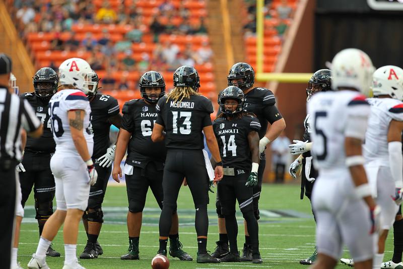 Hawaii quarterback Cole McDonald calls a play in the huddle against Arizona at Aloha Stadium on August 24, 2019, in Honolulu, Hawaii.