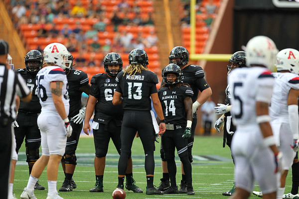 Hawaii quarterback Cole McDonald calls a play in the huddle against Arizona at Aloha Stadium on August 24, 2019, in Honolulu, Hawaii.