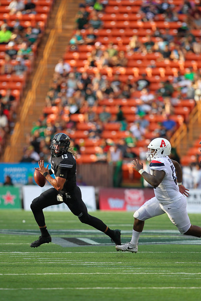 Hawaii quarterback Cole McDonald (13) scrambles from Arizona defensive end JB Brown (12) at Aloha Stadium on August 24, 2019, in Honolulu, Hawaii.