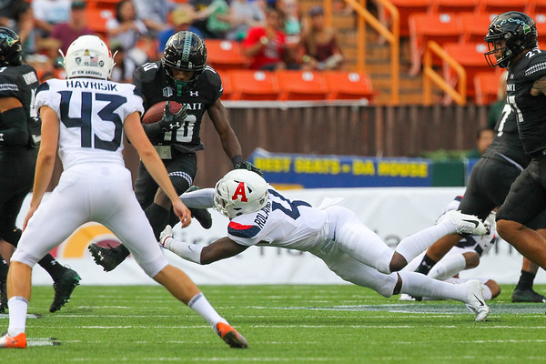 Hawaii receiver Maurice Stovall (10) avoids the tackle of Arizona's Christian Roland-Wallace (4) during a kickoff return at Aloha Stadium on August 24, 2019, in Honolulu, Hawaii.