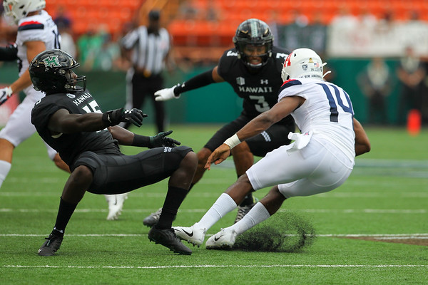 Arizona quarterback Khalil Tate jukes Hawaii linebacker Paul Scott (15) as defensive back Kalen Hicks (3) closes in at Aloha Stadium on August 24, 2019, in Honolulu, Hawaii.