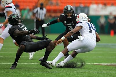 Arizona quarterback Khalil Tate jukes Hawaii linebacker Paul Scott (15) as defensive back Kalen Hicks (3) closes in at Aloha Stadium on August 24, 2019, in Honolulu, Hawaii.