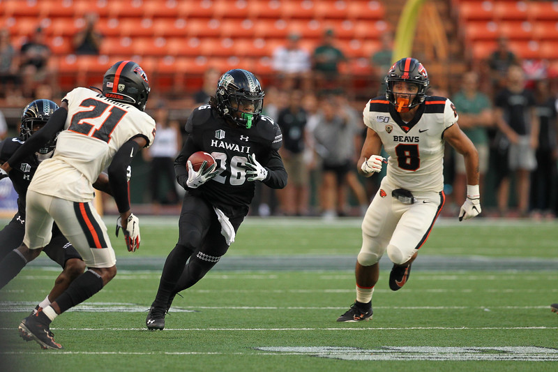 Hawaii running back Miles Reed rushes as Oregon State defenders Matthew Tago (8) and Nashon Wright (21) give chase at Aloha Stadium on September 7, 2019, in Honolulu, Hawaii.