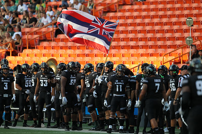 A Rainbow Warrior player waves the Hawaii state flag before the game against the Oregon State Beavers at Aloha Stadium on September 7, 2019, in Honolulu, Hawaii.