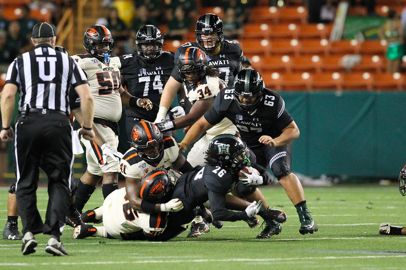 Hawaii running back Miles Reed (26) is gang-tackled after a rush up the middle against Oregon State at Aloha Stadium on September 7, 2019, in Honolulu, Hawaii.
