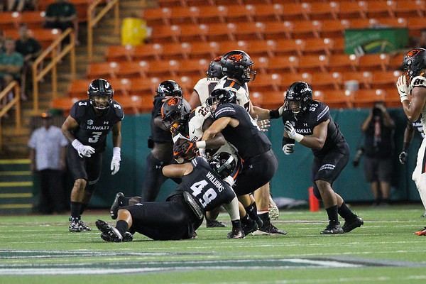 Oregon State running back Jermar Jefferson is brought down by Hawaii's Manly Williams (49) and teammate at Aloha Stadium on September 7, 2019, in Honolulu, Hawaii.