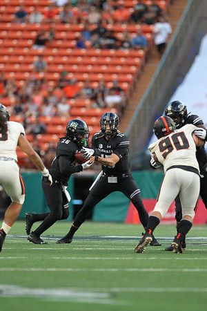Hawaii quarterback Cole McDonald hands the ball off to running back Miles Reed in first quarter action against Oregon State at Aloha Stadium on September 7, 2019, in Honolulu, Hawaii.