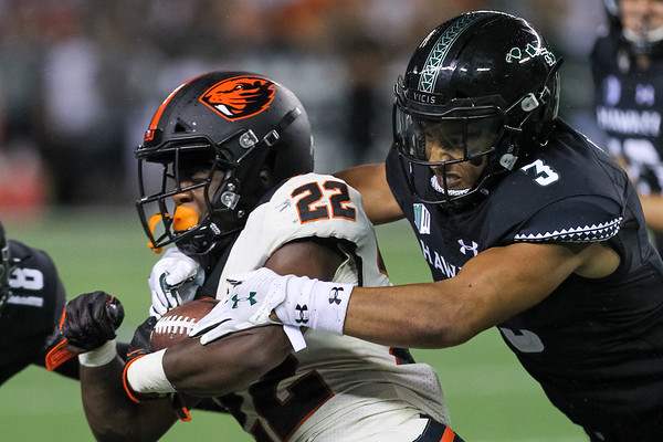 Oregon State running back Jermar Jefferson (22) is brought down for no gain by Hawaii's Kalen Hicks (3) at Aloha Stadium on September 7, 2019, in Honolulu, Hawaii.