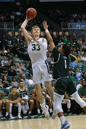 Kyle Colvin (33) turns baseline to shoot a jump hook over Drew Buggs (1) at the Stan Sheriff Center, Honolulu, Hawaii on January 16, 2020.