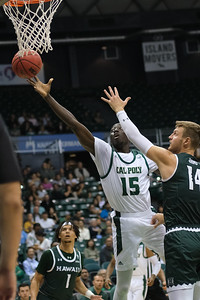 Cal Poly forward Alimamy Koroma (15) extends for a layup against the defense of Hawaii's Zigmars Raimo (14) at the Stan Sheriff Center, Honolulu, Hawaii on January 16, 2020.