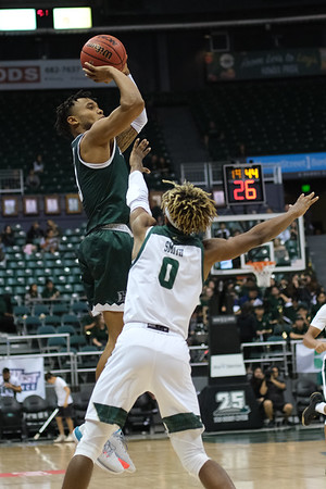Eddie Stansberry shoots a trey over Keith Smith at the Stan Sheriff Center, Honolulu, Hawaii on January 16, 2020. Stansberry was 3-9 from deep and led UH with 17 points.