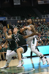 Cal Poly's bruiser Nolan Taylor (31) fights for the rebound with Hawaii's Dawson Carper (44) at the Stan Sheriff Center, Honolulu, Hawaii on January 16, 2020.