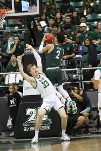 Justin Webster (2) of Hawaii draws contact on his way up for a layup against Kyle Colvin (33) of Cal Poly at the Stan Sheriff Center, Honolulu, Hawaii on January 16, 2020.