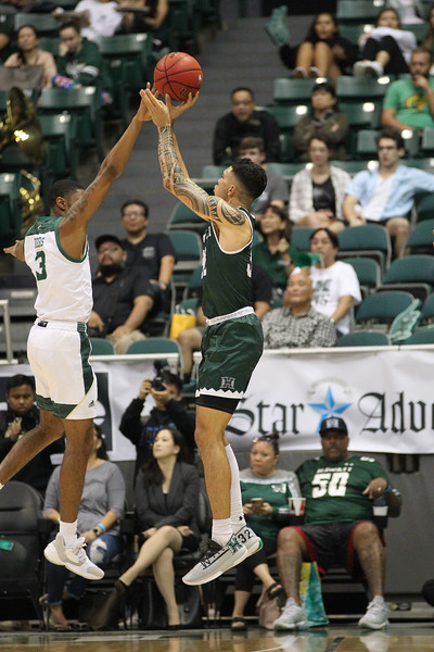 Samuta Avea (32) shoots over Colby Rogers (3) at the Stan Sheriff Center, Honolulu, Hawaii on January 16, 2020. Avea led Hawaii with a plus/minus of +18.