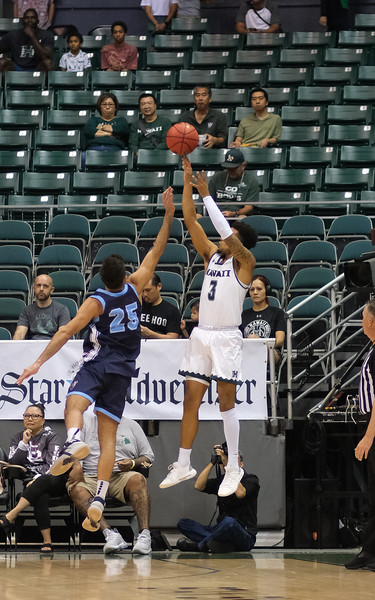 Hawaii guard Eddie Stansberry shoots a three pointer over Maine's Sergio El Darwich in the first half at the Stan Sheriff Center, Honolulu, Hawaii on December 29, 2019.