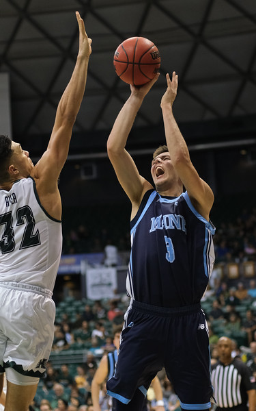 Maine's Vilgot Larsson attempts a shot over Hawaii's Samuta Avea at the Stan Sheriff Center, Honolulu, Hawaii on December 29, 2019. Avea blocked the attempt.