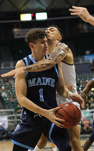 Maine guard Mykhailo Yagodin draws contact from Hawaii's Samuta Avea at the Stan Sheriff Center, Honolulu, Hawaii on December 29, 2019.