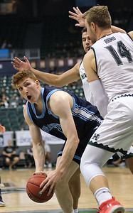 Maine forward Andrew Fleming looks for daylight from the double team of Hawaii's Zigmars Raimo (14) and Mate Colina at the Stan Sheriff Center, Honolulu, Hawaii on December 29, 2019.
