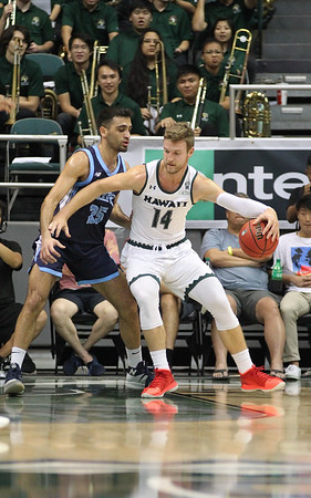 Hawaii forward Zigmars Raimo posts up against Maine's Sergio El Darwich at the Stan Sheriff Center, Honolulu, Hawaii on December 29, 2019.