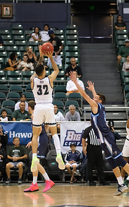 Hawaii's Samuta Avea shoots over Maines' Vilgot Larsson in first half action at the Stan Sheriff Center, Honolulu, Hawaii on December 29, 2019.