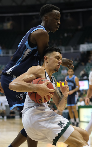 Hawaii's Samuta Avea secures the loose ball despite hard contact from Maine's Stephane Ingo at the Stan Sheriff Center, Honolulu, Hawaii on December 29, 2019.