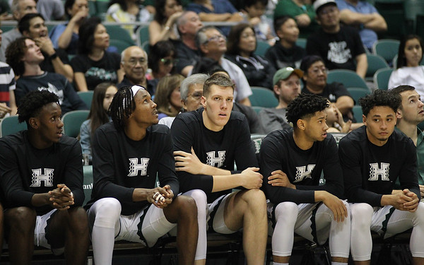 Players on Hawaii's bench look on as Hawaii battles Maine at the Stan Sheriff Center, Honolulu, Hawaii on December 29, 2019.
