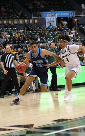Maine guard Sergio El Darwich drives against Hawaii guard Drew Buggs at the Stan Sheriff Center, Honolulu, Hawaii on December 29, 2019.