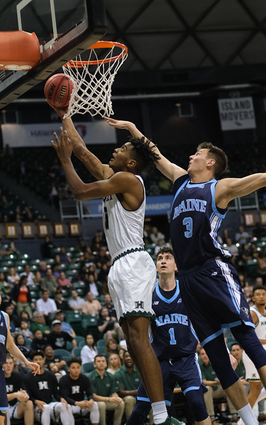 Hawaii's Bernardo Da Silva goes up for a reverse layup as Maine's Vilgot Larsson defends at the Stan Sheriff Center, Honolulu, Hawaii on December 29, 2019.